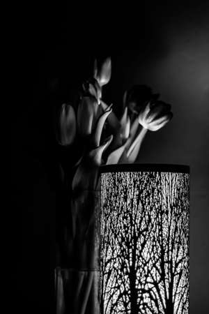 black and white photo of tulips in a vase behind a lamp with a forest motif. Greyscale photography