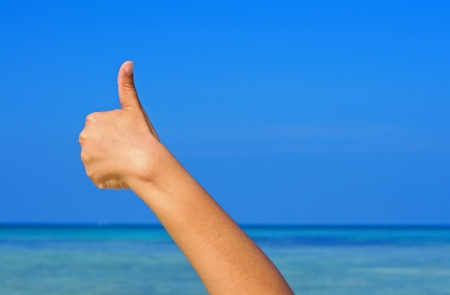 Hand making the sign of good with the blue sky and sea background Banco de Imagens