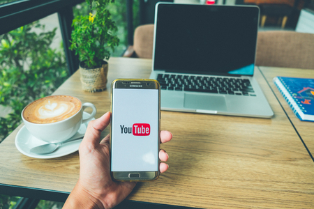 CHIANG MAI, THAILAND - June 26,2018: A Man holds Samsung Galaxy S7 edge Mobile Phone with Youtube application on the screen in coffee shop. YouTube is an video-sharing service website. Editorial