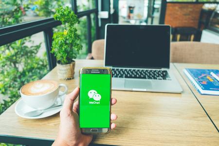 CHIANG MAI, THAILAND - 26 juni 2018: een man houdt een Samsung Galaxy S7 edge mobiele telefoon met WeChat-app op het scherm. WeChat is een Chinese multifunctionele app voor berichten, sociale media en mobiele betalingen Redactioneel