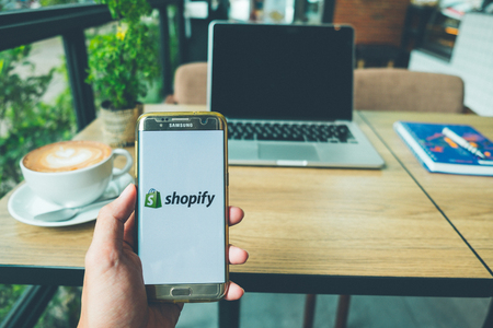 CHIANG MAI, THAILAND - June 26,2018: A Man holds Samsung Galaxy S7 edge Mobile Phone with Shopify application on the screen in coffee shop. Shopify is an e-commerce platform for online stores Editorial