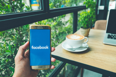 CHIANG MAI, THAILAND - June 26,2018: A Man holds Samsung Galaxy S7 edge Mobile Phone with Facebook application on the screen in coffee shop. Facebook is a social media and social networking app