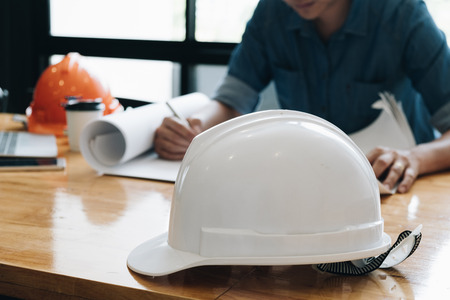 Safety helm with Yong architect man working with blueprints, yong engineer inspection in workplace for architectural plan project,sketching a construction project ,Business concept Standard-Bild