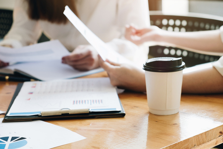 Hot Coffee Cup focus ,Business People Meeting Conference Discussion Start up Project Plan with paperwork in wordspace Corporate Concept