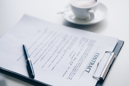 Pen on contract sheet and business document ,near coffee cup in home office, Business and Office concept.