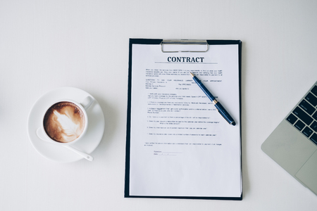 Pen on contract sheet and business document ,near coffee cup and laptop computer in home office, Business and Office concept.