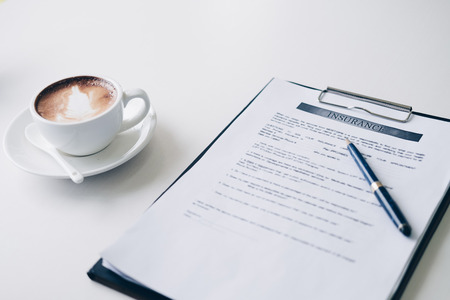 Pen on Insurance contract document sheet and business document ,near coffee cup and laptop computer in home office, Business and Office concept.