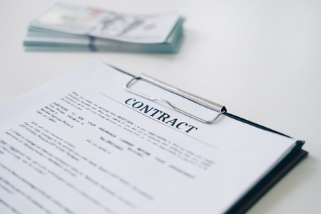 Insurance contract document sheet and business document with money in background in home office, Business and Office concept.