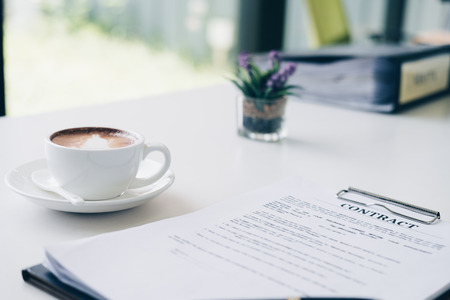 Contract document sheet and business document ,near coffee cup latte art in home office, Business and Office concept. Standard-Bild