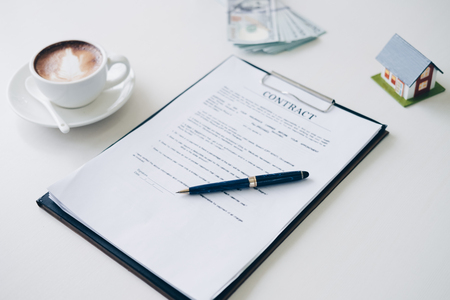 Pen on House insurance document and contract document near coffee cup latte art with money in background in home office, Business and Office concept.