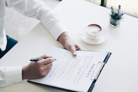 Businessmen holding pen to write business document and contract sheet while sitting at desk with coffee cup in home office, Business and Office concept.