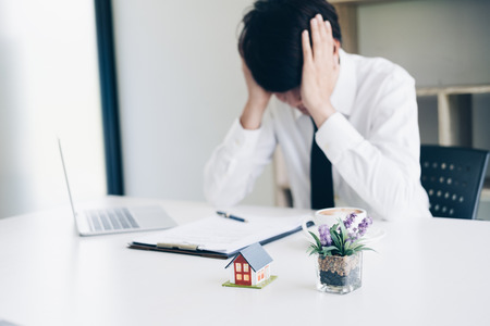 Frustrated business man stress when fail with real estate agent work while sitting at desk with laptop, paperwork and coffee cup in home office, Business and Office concept. Standard-Bild