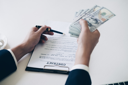 Man's hand in suit giving cash money and using pen point to signing a mortgage loan agreement in office, Mortgage and Home Loan concept.