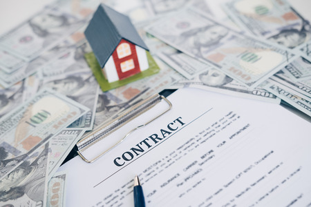 One hundred dollar bill and contract with pen in the middle, Mortgage and Home Loan concept. Standard-Bild