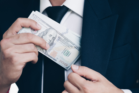 Business man in Suits receiving large amount of US banknotes as a bribe, Corruption in Business concept.