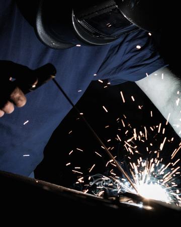 Man welding iron with a protective mask. Dramatic sparkles and smoke Zdjęcie Seryjne