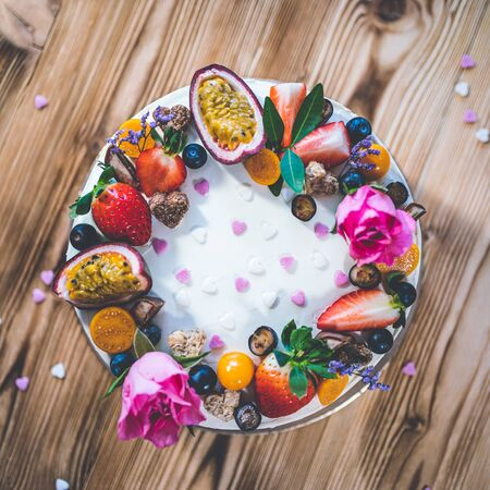 Sweet white cheesecake torte with fresh fruits, poppy and rose flowers on wooden table background. Ideal gift for birthday, Valentine day and celebration 版權商用圖片