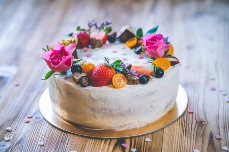 Sweet white cheesecake torte with fresh fruits, poppy and rose flowers on wooden table background. Ideal gift for birthday, Valentine day and celebration Standard-Bild - 140584930