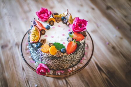 Sweet white cheesecake torte with fresh fruits, poppy and rose flowers on wooden table background. Ideal gift for birthday, Valentine day and celebration Standard-Bild