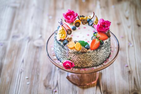 Sweet white cheesecake torte with fresh fruits, poppy and rose flowers on wooden table background. Ideal gift for birthday, Valentine day and celebration Standard-Bild - 140584993