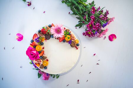 Sweet white cheesecake torte with fresh fruits and rose flowers on white wooden table background. Ideal gift for birthday, name-day, Valentine, and celebration.