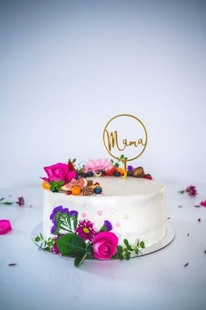Sweet white cheesecake torte with fresh fruits and rose flowers on white wooden table background. Ideal gift for mother mama birthday, name-day and celebration. Archivio Fotografico