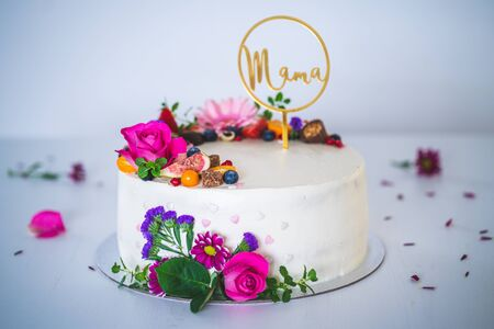 Sweet white cheesecake torte with fresh fruits and rose flowers on white wooden table background. Ideal gift for mother mama birthday, name-day and celebration. Standard-Bild