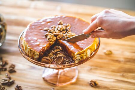 Woman confectioners hand slice homemade chessecake with caramel topping and walnut nuts on wooden table. Tasty brown cake dessert.