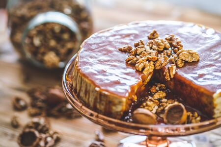Sweet homemade chessecake with caramel topping and walnut nuts on wooden table. Tasty brown cake dessert.