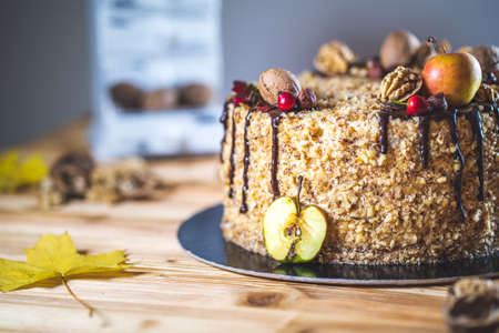 Sweet homemade nuts cake with chocolate topping and walnut nuts and apple on wooden autumn vintage table Tasty unhealthy dessert Front detail view