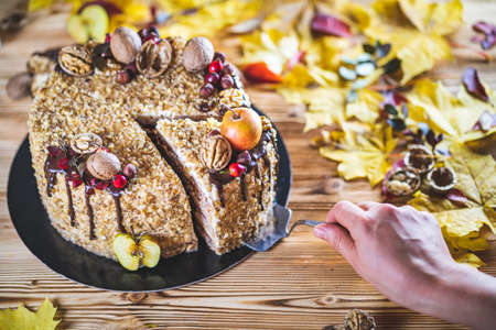 Woman hand take Slice Sweet homemade nuts cake with chocolate topping and walnut nuts and apple on wooden autumn vintage table Tasty unhealthy dessert Front view