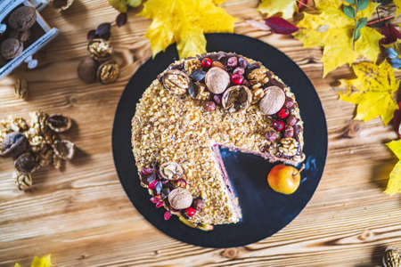 Sweet homemade nuts cake with chocolate topping and walnut nuts eat apple on wooden autumn vintage table Tasty unhealthy dessert Front view Archivio Fotografico