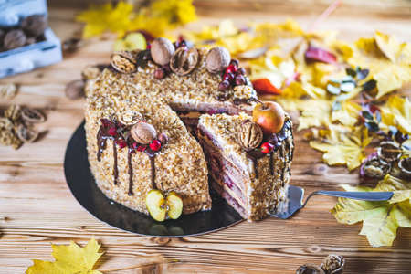 Sweet homemade nuts cake with chocolate topping and walnut nuts and apple on wooden autumn vintage table Tasty unhealthy dessert Front view