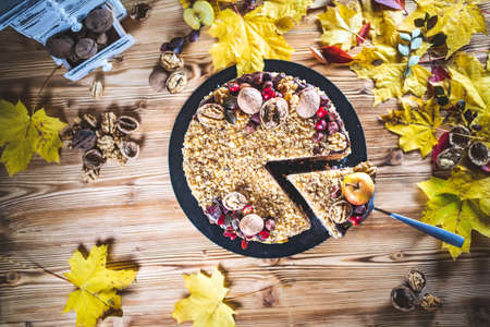 Sweet homemade nuts cake with chocolate topping and walnut nuts and apple on wooden autumn vintage table Tasty unhealthy dessert Top view