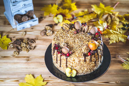 Sweet homemade nuts cake with chocolate topping and walnut nuts and apple on wooden vintage table with autumn decoration Tasty unhealthy dessert Front view