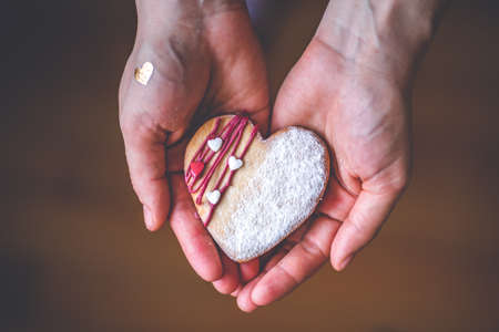 Woman hands hold sweet heart cake in her hands. Symbol of love