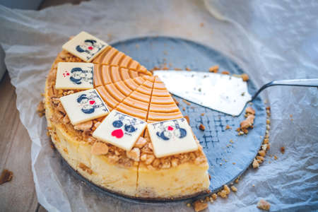 Slices of Sweet caramel cheesecake with with chocolate of young couple in love on bake paper wooden table