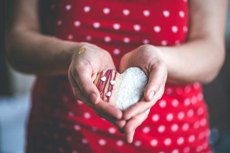 Woman in red shirt holds heart cake in hands, Symbol of love giving Archivio Fotografico