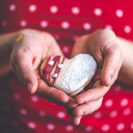 Woman in red shirt hold sweet heart cake in her hands