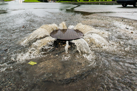 Accident sewerage system. Water flows over the road from the sewer. Stock Photo