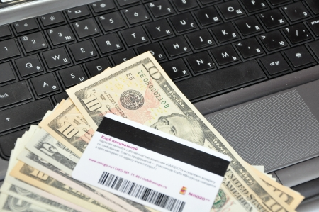 banknotes and credit card on top of a laptop