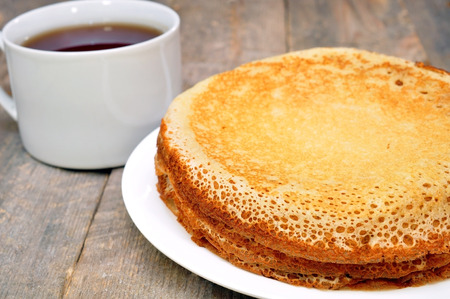 pancakes on a plate on a wooden table and a cup of tea Stock Photo