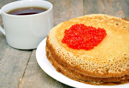 pancakes with red caviar and a cup of tea photo