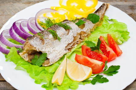 hake: fish hake baked with vegetables on a plate