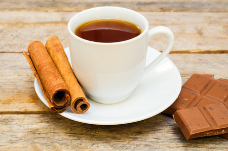 cup of tea with chocolate and cinnamon on wooden table