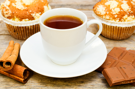muffins with tea, cinnamon sticks and chocolate on wooden table