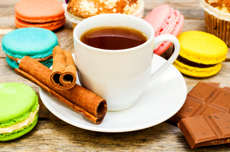 macaroon with tea, chocolate and cinnamon sticks on a wooden table