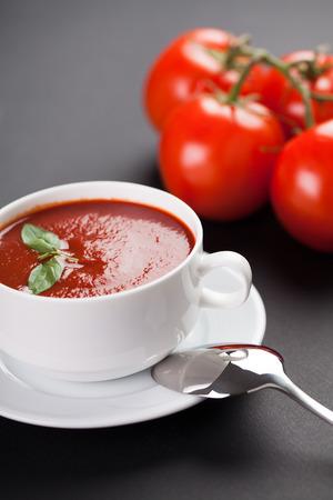 Fresh tomato soup on a black table photo
