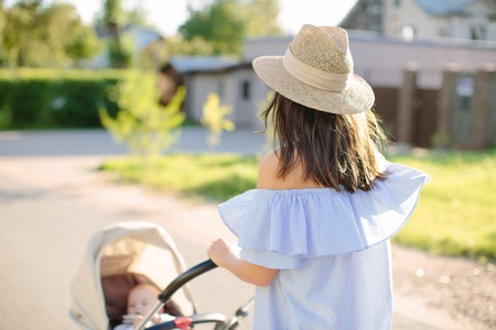 Young mother carries a child in a stroller. Look from behind