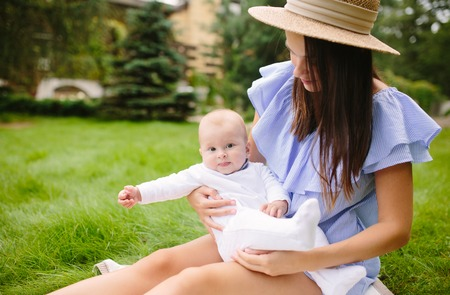 Young mother with newborn baby on the grass 写真素材